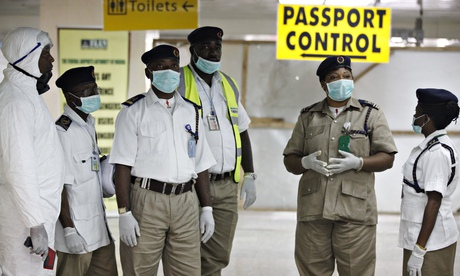 Health officials wait to screen passengers at the arrival hall of Lagos airport. Photograph: Sunday Alamba/AP