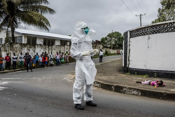 A young girl suspected of Ebola is left in the middle of the street by her aunt in Monrovia, Liberia. A medical worker prepares to transport her.